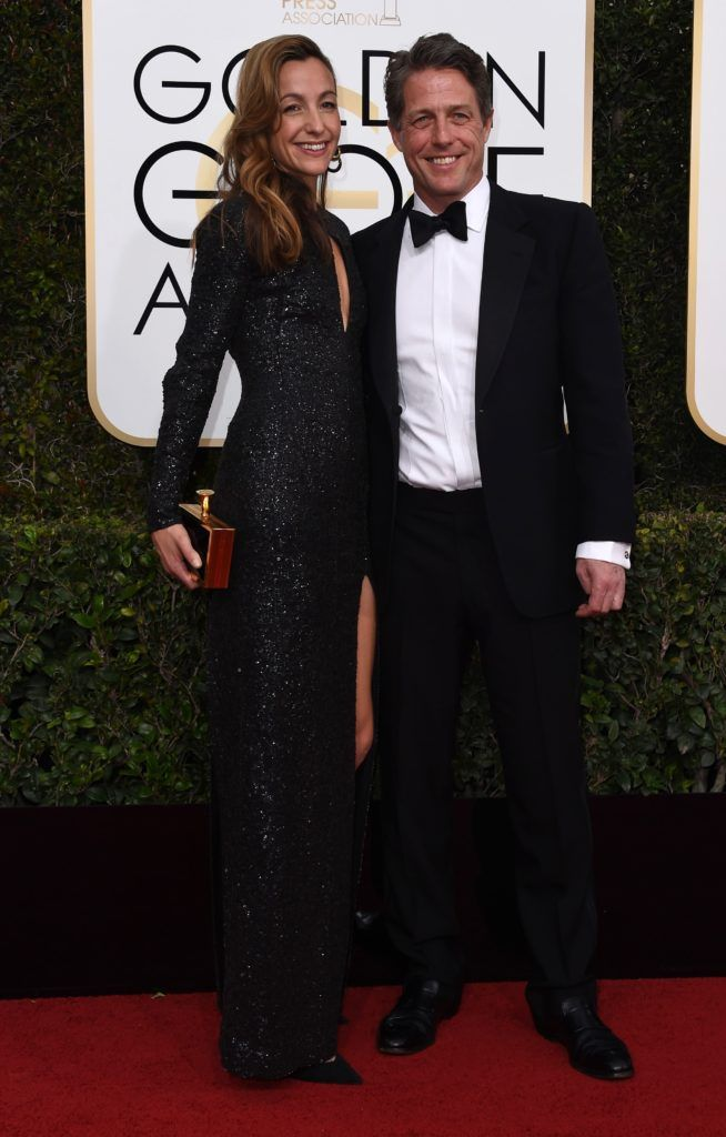 Hugh Grant (R) and  Anna Elisabet Eberstein arrive at the 74th annual Golden Globe Awards, January 8, 2017, at the Beverly Hilton Hotel in Beverly Hills, California.       (Photo VALERIE MACON/AFP/Getty Images)