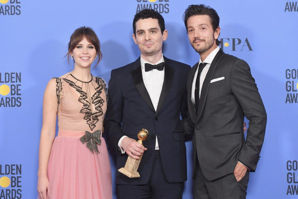 BEVERLY HILLS, CA - JANUARY 08:  Writer/director Damien Chazelle (C), winner of Best Screenplay for 'La La Land,' poses in the press room with actors Felicity Jones (L) and Diego Luna (R) during the 74th Annual Golden Globe Awards at The Beverly Hilton Hotel on January 8, 2017 in Beverly Hills, California.  (Photo by Kevin Winter/Getty Images)