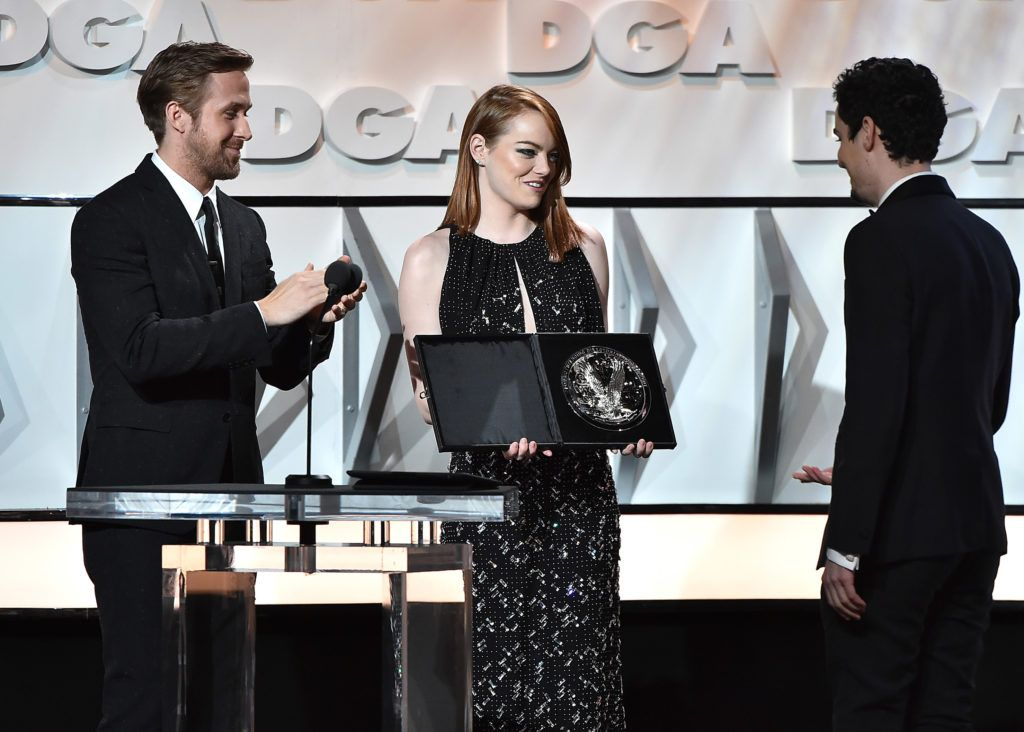 "Ryan Gosling and Emma Stone present the Feature Film Nomination Plaque for ""La La Land"" to director Damien Chazelle onstage during the 69th Annual Directors Guild of America Awards at The Beverly Hilton Hotel on February 4, 2017 in Beverly Hills, California.  (Photo by Alberto E. Rodriguez/Getty Images for DGA)"