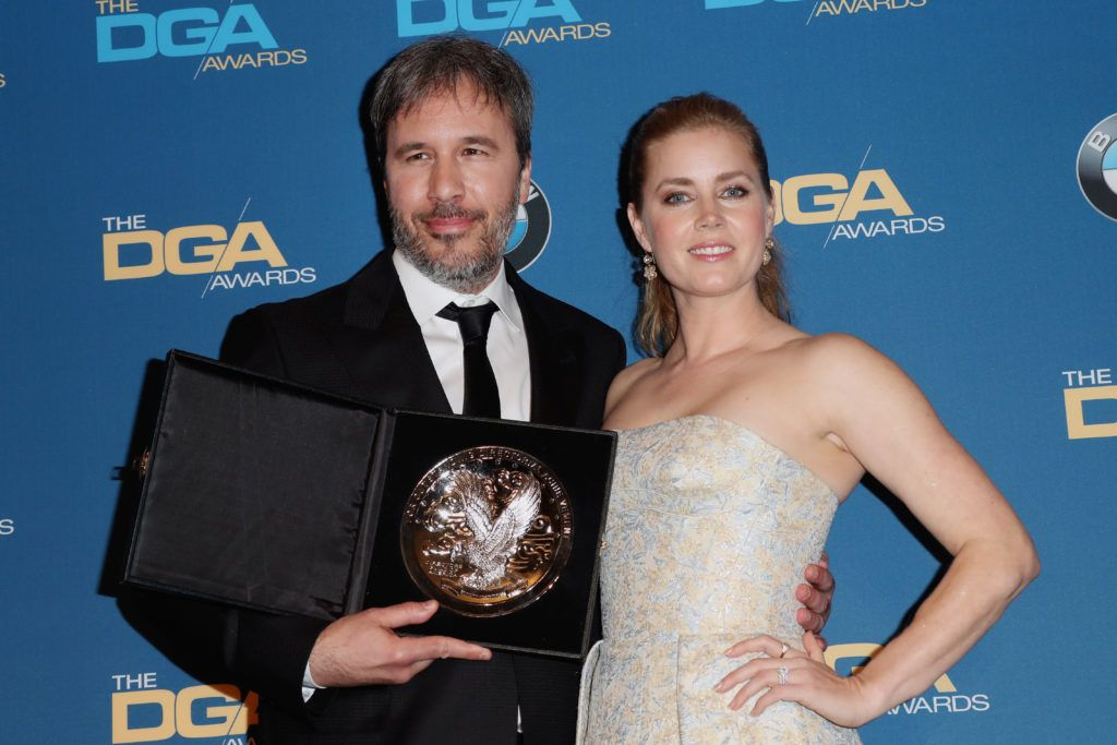 """Director Denis Villeneuve (L), recipient of the Feature Film Nomination Plaque for """"Arrival,"""" poses with actress Amy Adams in the press room during the 69th Annual Directors Guild of America Awards at The Beverly Hilton Hotel on February 4, 2017 in Beverly Hills, California.  (Photo by Frederick M. Brown/Getty Images)"""