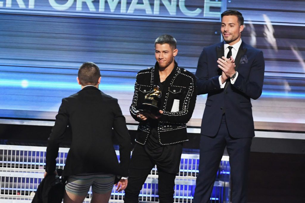 LOS ANGELES, CA - FEBRUARY 12:  Recording artist Nick Jonas (C) presents the the Best Pop Duo/Group Performance award for 'Stressed Out' to recording artist Tyler Joseph (L) of music group Twenty One Pilots onstage during The 59th GRAMMY Awards at STAPLES Center on February 12, 2017 in Los Angeles, California.  (Photo by Kevin Winter/Getty Images for NARAS)