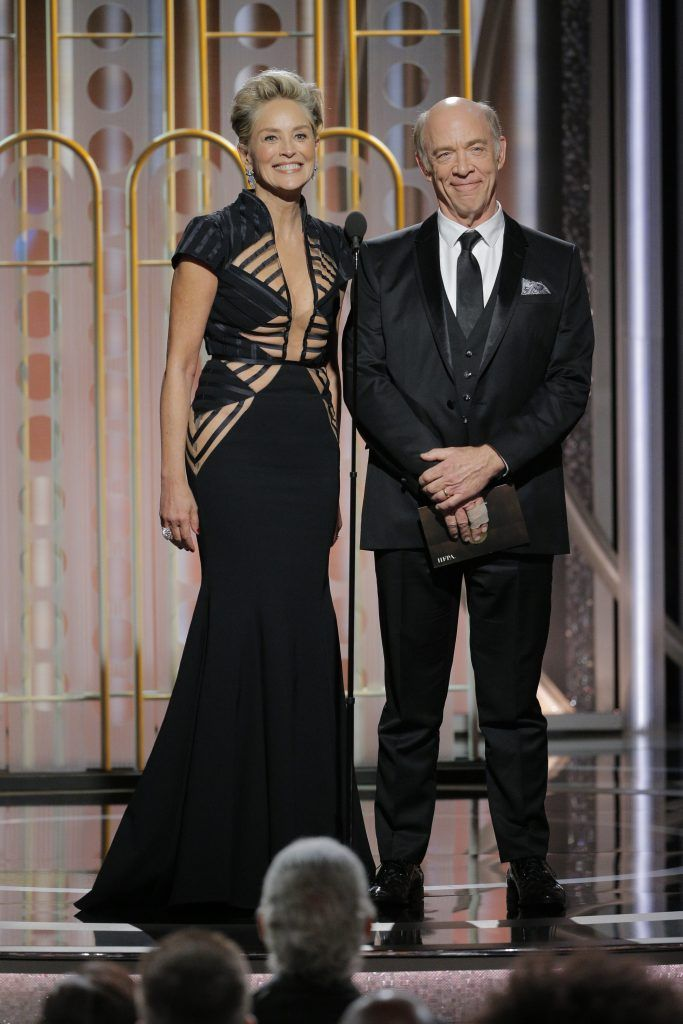 BEVERLY HILLS, CA - JANUARY 07:  In this handout photo provided by NBCUniversal,  Presenters Sharon Stone and J.K. Simmons speak onstage during the 75th Annual Golden Globe Awards at The Beverly Hilton Hotel on January 7, 2018 in Beverly Hills, California.  (Photo by Paul Drinkwater/NBCUniversal via Getty Images)