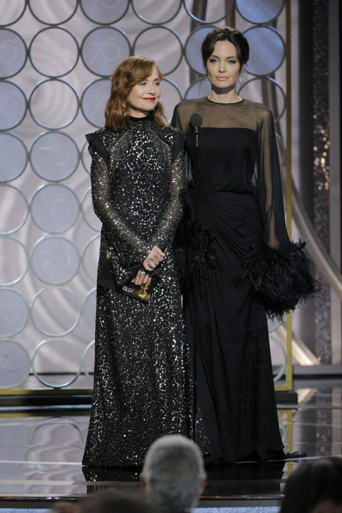 BEVERLY HILLS, CA - JANUARY 07:  In this handout photo provided by NBCUniversal,  Presenters Isabelle Huppert and  Angelina Jolie speak onstage during the 75th Annual Golden Globe Awards at The Beverly Hilton Hotel on January 7, 2018 in Beverly Hills, California.  (Photo by Paul Drinkwater/NBCUniversal via Getty Images)