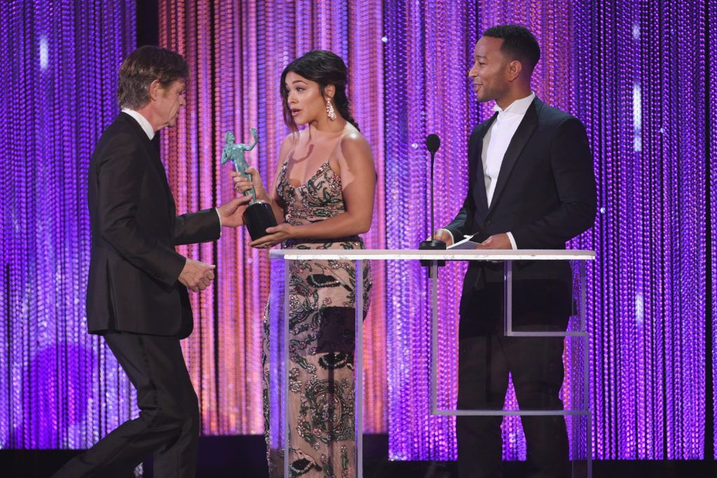 LOS ANGELES, CA - JANUARY 29:  Actor William H. Macy (L) accepts Outstanding Performance by a Male Actor in a Comedy Series for 'Shameless' from actor Gina Rodriguez (C) and actor/singer John Legend (R) onstage during The 23rd Annual Screen Actors Guild Awards at The Shrine Auditorium on January 29, 2017 in Los Angeles, California. 26592_014  (Photo by Kevin Winter/Getty Images )