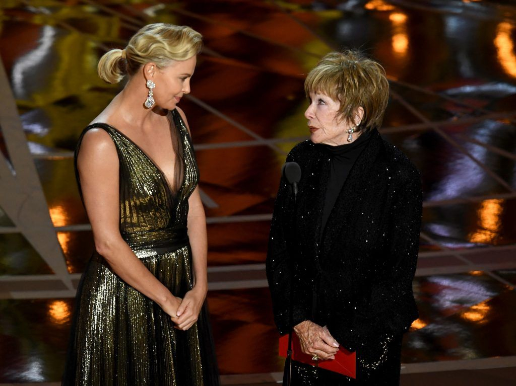 HOLLYWOOD, CA - FEBRUARY 26:  Actors Charlize Theron (L) and Shirley MacLaine speak onstage during the 89th Annual Academy Awards at Hollywood & Highland Center on February 26, 2017 in Hollywood, California.  (Photo by Kevin Winter/Getty Images)