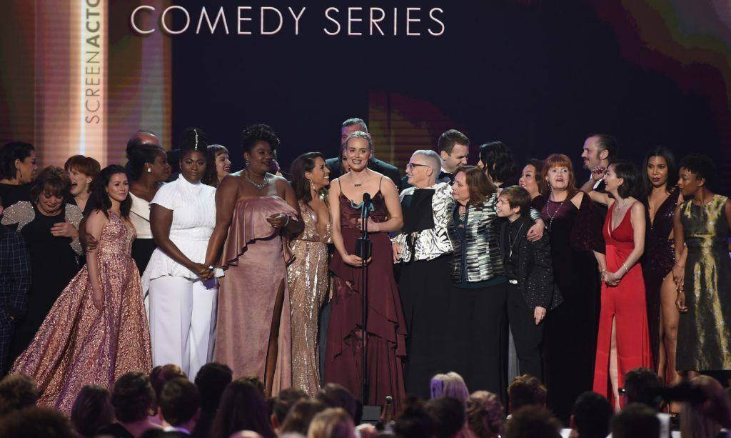 Actress Taylor Schilling (C) and the cast of 'Orange Is the New Black' accept the award for Outstanding Performance by an Ensemble in a Comedy Series onstage during the 23rd Annual Screen Actors Guild Awards show at The Shrine Auditorium on January 29, 2017 in Los Angeles, California. (Photo ROBYN BECK/AFP/Getty Images)