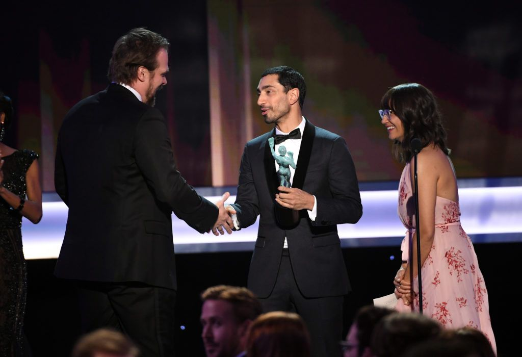LOS ANGELES, CA - JANUARY 29:  (L-R) Actor David Harbour of 'Stranger Things' accepts Outstanding Performance by an Ensemble in a Drama Series from actors Riz Ahmed and Rashida Jones onstage during The 23rd Annual Screen Actors Guild Awards at The Shrine Auditorium on January 29, 2017 in Los Angeles, California. 26592_014  (Photo by Kevin Winter/Getty Images )