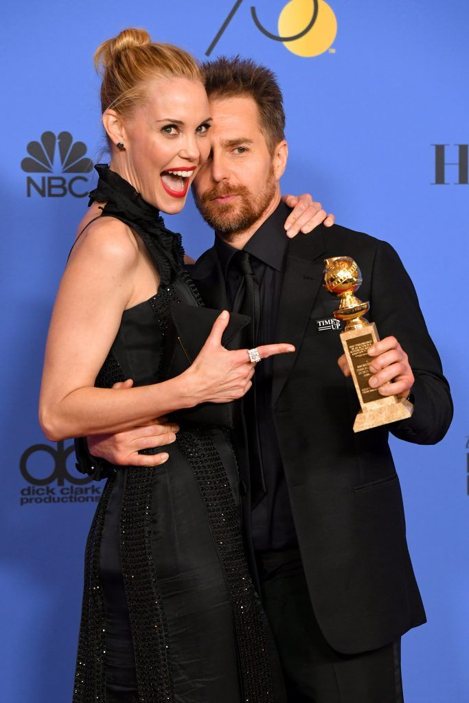 BEVERLY HILLS, CA - JANUARY 07:  Leslie Bibb poses with actor Sam Rockwell holding his award for Best Performance by an Actor in a Supporting Role in any Motion Picture for 'Three Billboards Outside Ebbing, Missouri' in the press room during The 75th Annual Golden Globe Awards at The Beverly Hilton Hotel on January 7, 2018 in Beverly Hills, California.  (Photo by Kevin Winter/Getty Images)