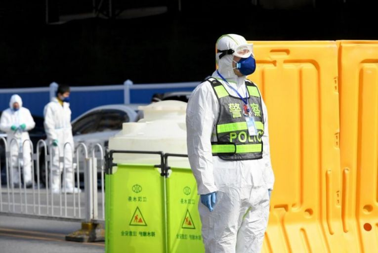 A police officer watches disinfection work at Huanan Wholesale Seafood Market. The Chinese government has essentially locked down Hubei province. Picture: Visual China Group via Getty Images