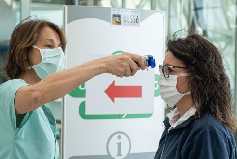 A nurse takes a woman's temperature at a Padua hospital. Italy is planning a slow return to normal life. Picture: NurPhoto via Getty Images