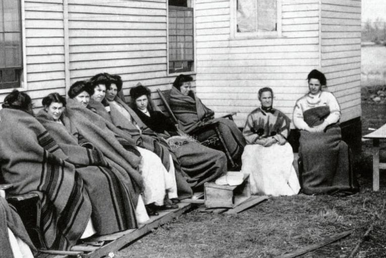 Mary Mallon, better known as Typhoid Mary, sits fourth from right among a group of inmates quarantined on an isolated island on the Long Island Sound. Picture: Science History Images/Alamy Stock Photo