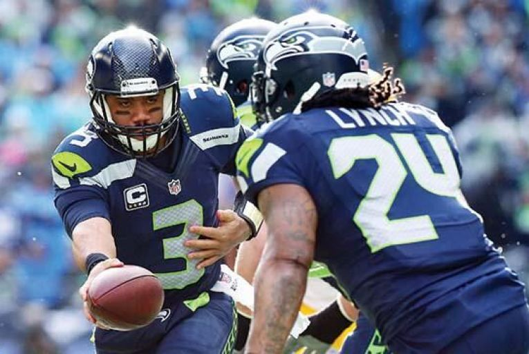 Russell Wilson of the  Seattle Seahawks hands the ball to team-mate Marshawn Lynch during their 28-22 win over the Green Bay Packers a fortnight ago. Picture: Getty