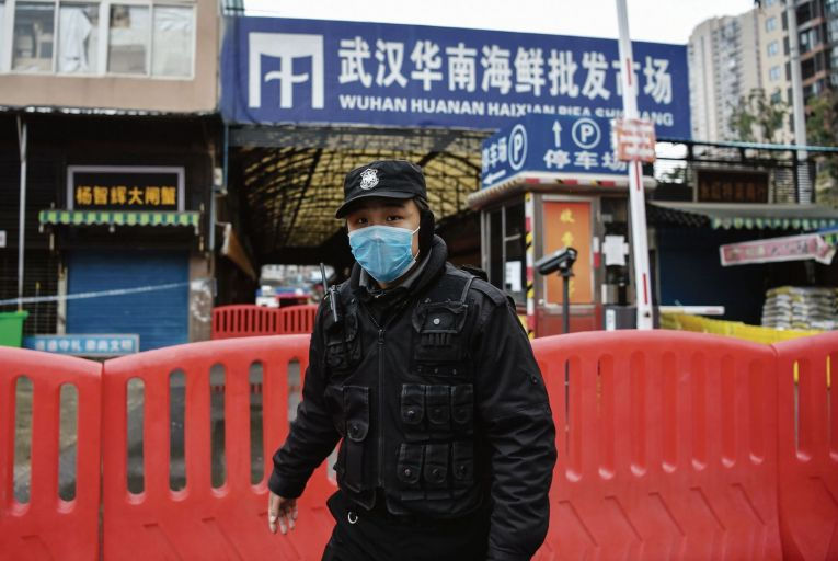 A police officer stands guard outside Huanan Seafood Wholesale market where the coronavirus was detected in Wuhan in China Pic: Getty