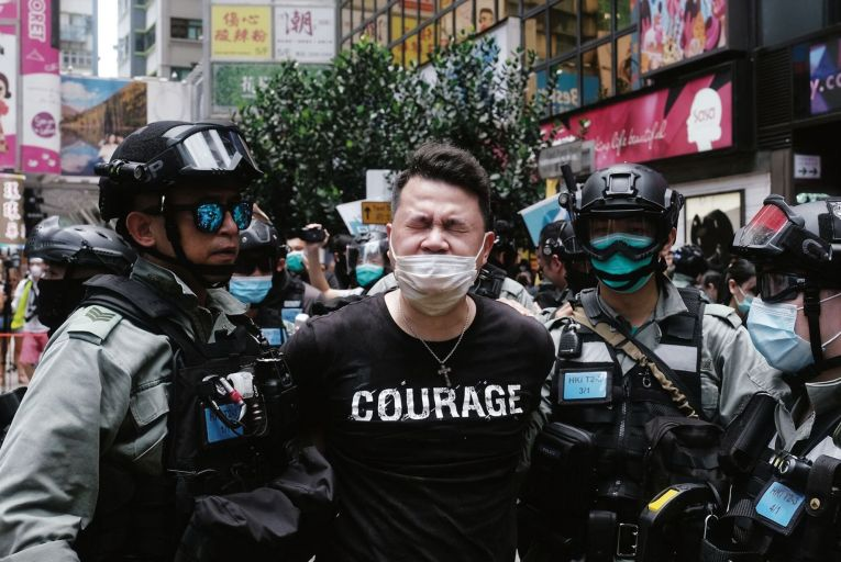 Andrew Wan, a pro-democracy lawmaker, is arrested by riot police during a protest in Hong Kong, China, last year. Photographer: Roy Liu/Bloomberg