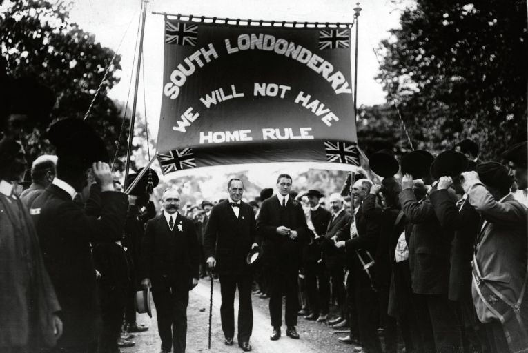 Unionists Hugh T Barrie, Edward Carson and Frederick Smith are cheered on by supporters at an Anti-Home Rule demonstration in Derry city in September 1912. Picture: Getty