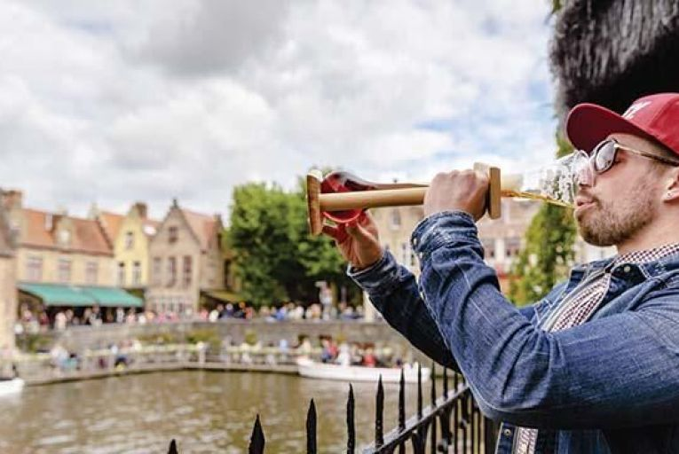 A tourist knocks back some Belgian beer by a canal in Brussels.