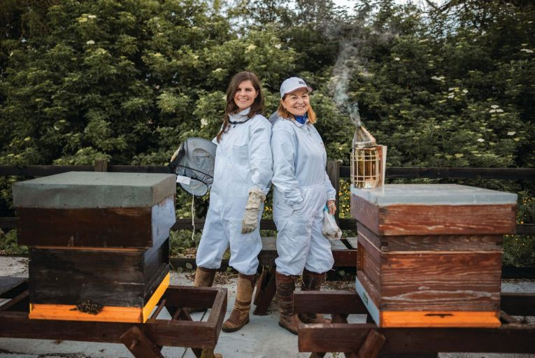 Sally Anne Cooney and her mother Marie Cooney with some of the beehives at the family\'s lands in Kilmessan, Co Meath. Their new gin, Silks Gin, has its origin in beekeeping.