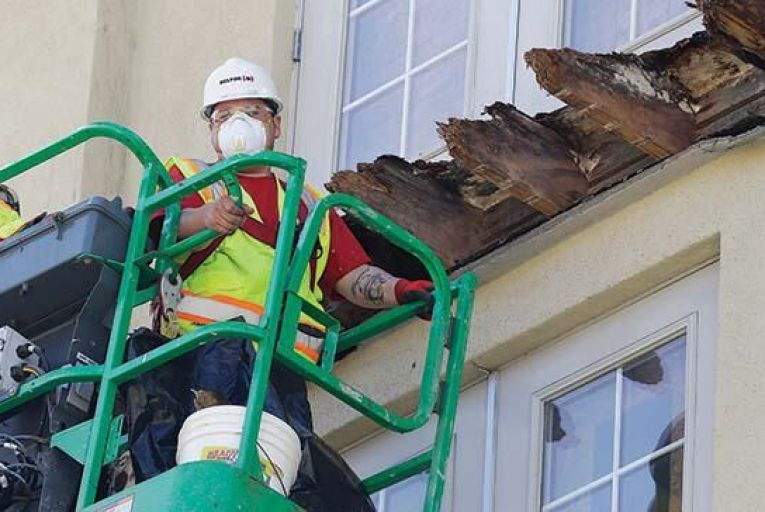 Workmen examine the remains of the wooden balcony supports at the Library Gardens apartment building in Berkeley AP