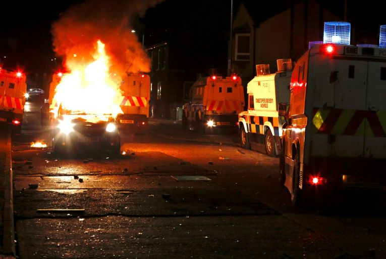 Flames rise from a car set on fire in Belfast where 88 police officers have been injured during the violence over the past week