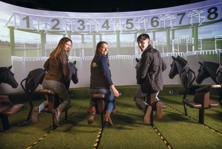 Emma Hannon, Ellen Mitchell and Conor Hyland take part in a virtual horse race at the Irish Racehorse Experience