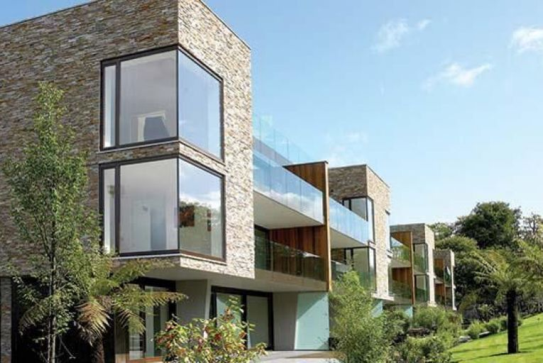Locally-quarried limestone and native wood form the facade of the apartments