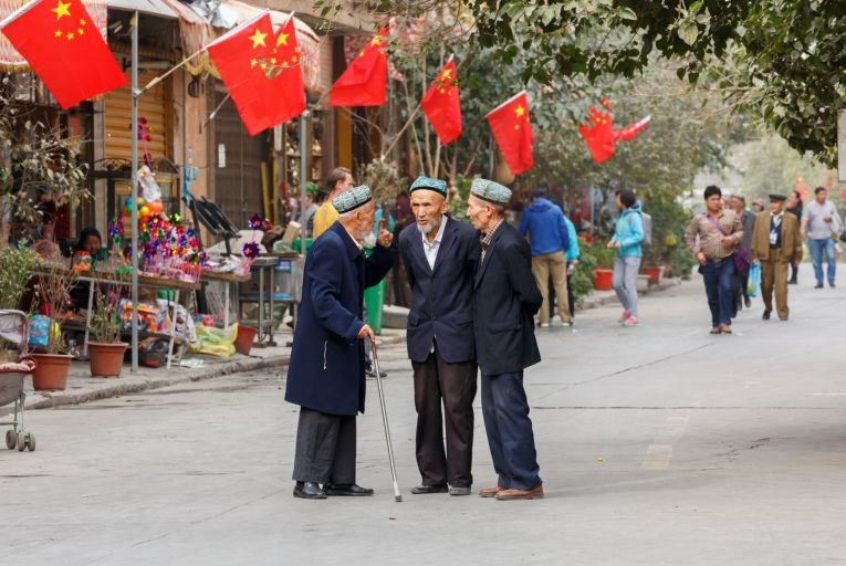 Three men of the Uyghur minority having a conversation in Kashgar in Xianjiang: the Uyghur Muslims in China have been subject to human rights abuses, with an estimated one million in detention camps. Photo: Getty