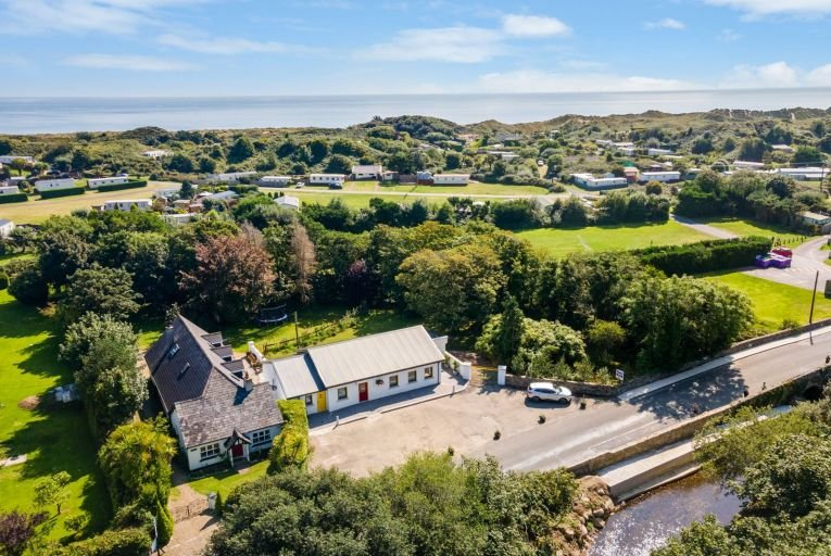 'The residence is a charming cottage which was tastefully extended in the mid-1990s and comprises six bedrooms, two spacious reception rooms, a family kitchen with a utility and three bathrooms'