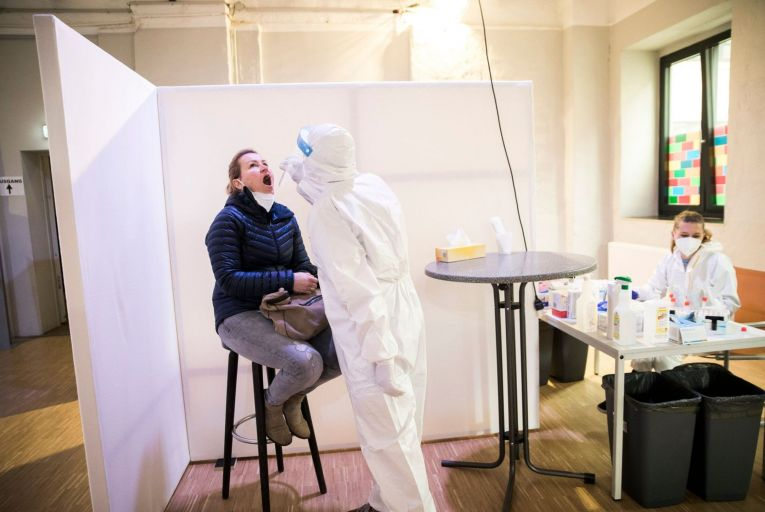 A member of staff of the Ritter Butzke bar in Germany takes a rapid antigen test from a woman at a Covid-19 testing station set up by the bar for customers. Picture: Getty