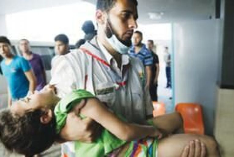 A Palestinian medic carries a wounded girl into the Shifa hospital in Gaza City last Friday. Picture: AP Photo