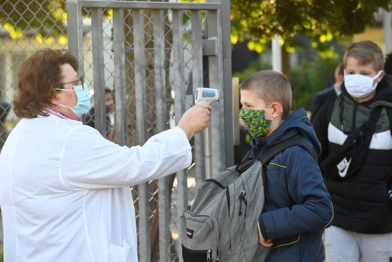 A member of the educational team checks body temperature of a schoolboy in France PIctue: Getty