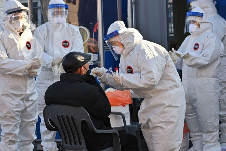Medical staff member wearing protective gear take a swab from a man to test for the Covid-19 coronavirus at a temporary testing station in Seoul, South Korea. Picture: Getty