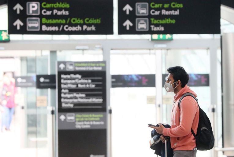 """A man wears a facemask at Dublin Airport's arrivals hall. Leo Varadkar told the Dáil that the government would consider """"employment supports"""" for workers who were self-isolating. Picture: Brian Lawless/PA"""