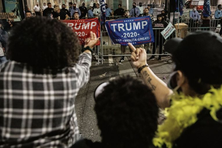 People celebrating the election victory of Joe Biden in the US presidential election taunt supporters of Donald Trump outside the Philadelphia Convention Centre. Pic: Getty