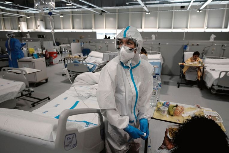 A healthcare worker attends to a patient at the Covid-19 wing of the Enfermera Isabel Zendal new emergency hospital, in Madrid Picture: Getty