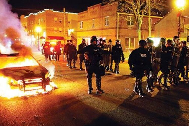 Police in riot gear  move past a burning  vehicle in Ferguson Picture: EPA/AP
