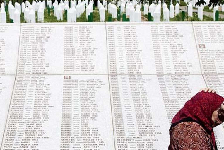 A woman in front of a stone tablet at the Srebrenica Memorial, with the names of those killed in July 2005 when Serbian units under General Ratko Mladic murdered about 8,000 Muslims. Picture: Getty