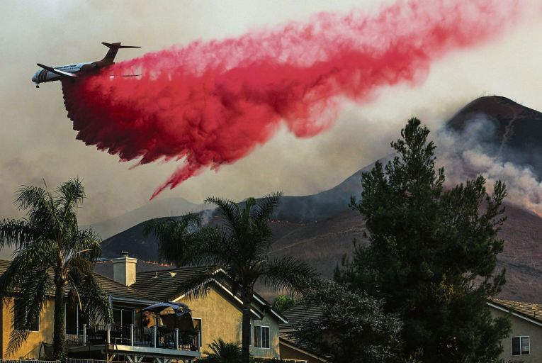 An air tranker drops fire retardant on homes during a huge fire in Chino Hills in Calofornia last month Pic: Getty
