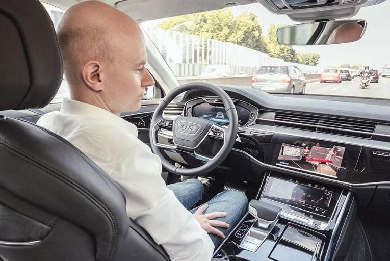 Watching television on the go in the new Audi A8, which is equipped with  Level Three  autonomous driving