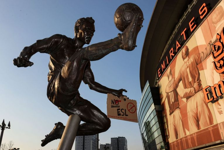 A sign protesting the European Super League taped to the hand of the Dennis Bergkamp statue outside Arsenal's Emirates Stadium. Picture: Getty