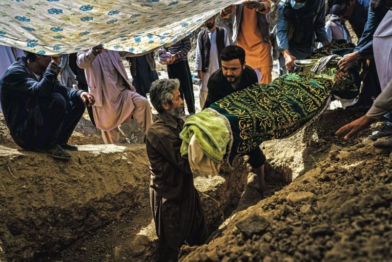 Relatives of one of those killed in the suicide attacks at Kabul Airport, bury his body on Martyrs Hill on the outskirts of Kabul. Picture: Getty