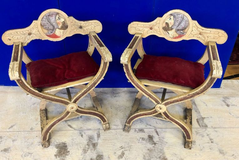A pair of X-shaped chairs decorated with images of warriors are estimated at €150-€250