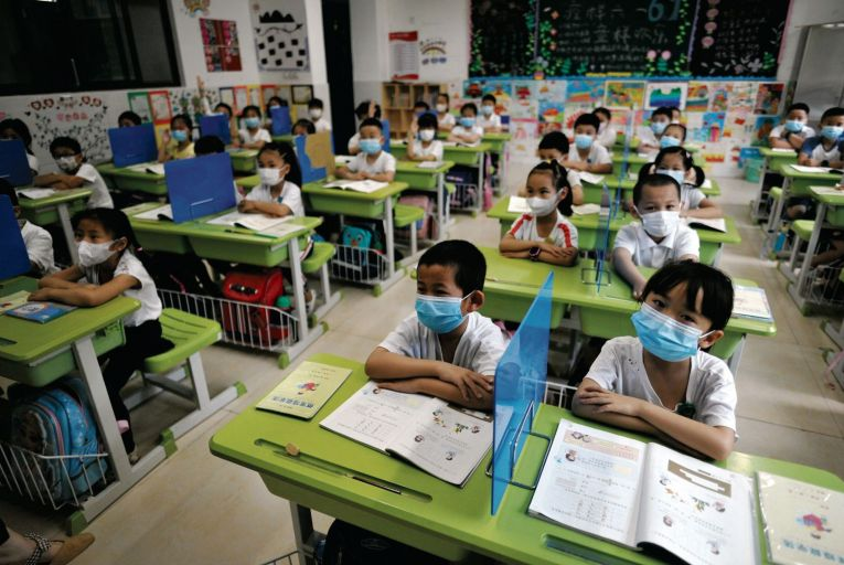 Primary schoolchildren in the Chinese city of Fuzhou wear facemasks on the first day of their school's reopening last week. Picture: Getty