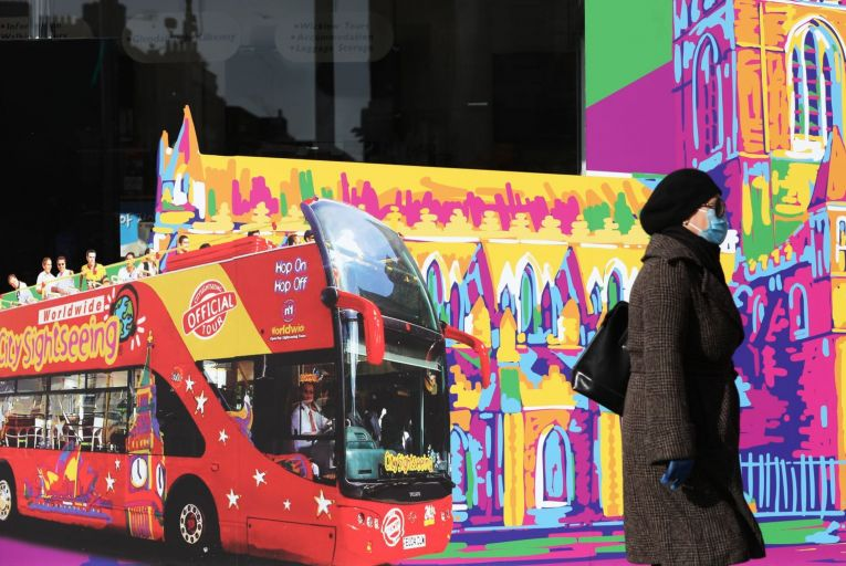A woman wears a face mask as she passes by a tourism ad on Dublin's O'Connell Street. Face coverings could reduce the amount of droplet expelled from a person's nose and mouth, and may help reduce the spread of the virus. Picture: Rollingnews.ie