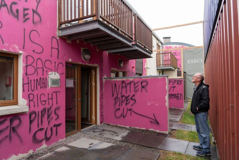 Council orders hotel to remove shipping containers from front of homes