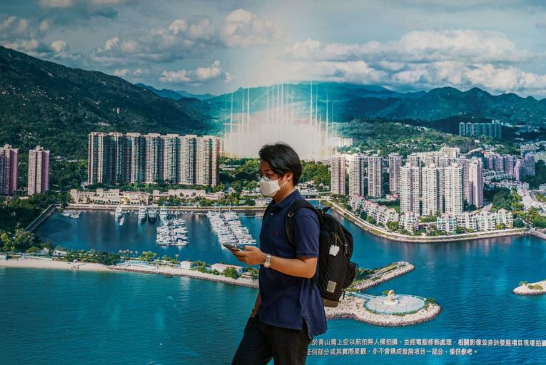 A man walks past a banner outside the China Evergrande Centre in Hong Kong: the experience of Ireland and Spain, where property bubbles burst with devastating consequences in the financial crash of 2008, has direct relevance to what is happening in China. Picture: Bloomberg