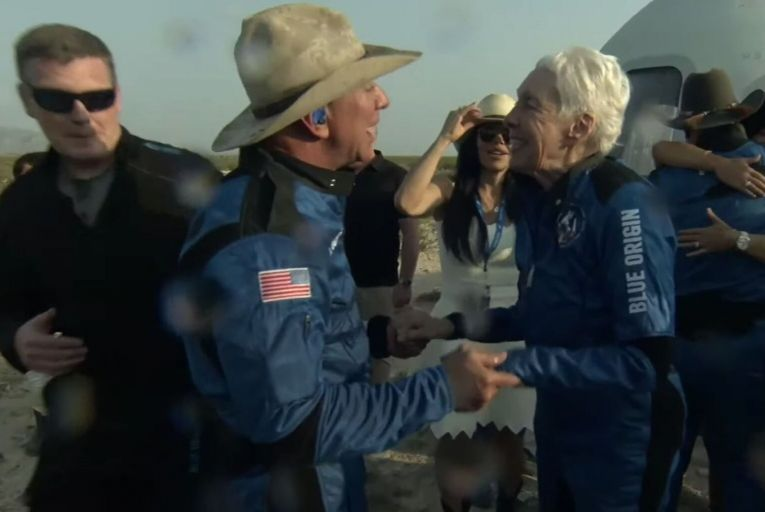 Jeff Bezos and 82-year-old Wally Funk celebrated as they leave Blue Origin's New Shepard crew capsule after the first human spaceflight for the company. Picture: Getty