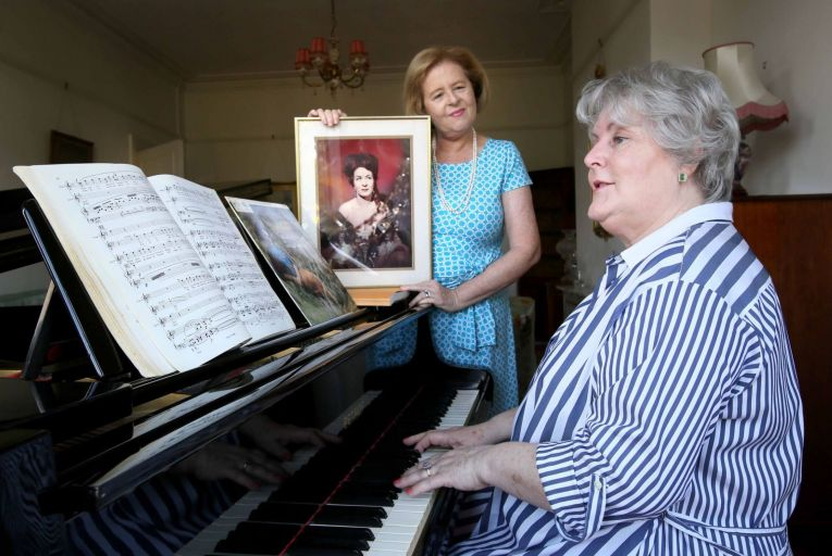 Judy Gaughan, the daughter Veronica 'Ronnie' Dunne's daughter, holds a picture of the late soprano, as Dr Angela Feeney, soprano and a former student of Veronica Dunne, plays a Petrof Grand Piano gifted by Dunne's family to the RIAM. Picture: Mark Stedman