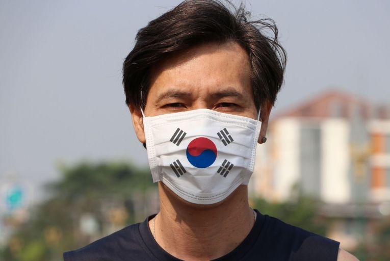A South Korean man wears a mask with the country's flag on it: South Korea has prevented a disruptive nationwide epidemic, containing occasional flare-ups as they have arisen. Picture: Getty