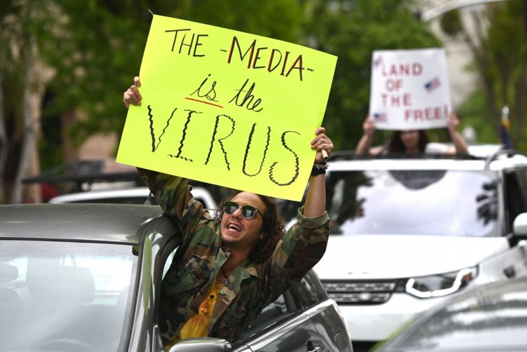 A man holds an anti-media sign during a protest against lockdown measures in California. Protesters rejected the government's advice by gathering in close proximity. Surveys have shown that trust is many institutions, including the media, is low in the US. Picture: Getty.