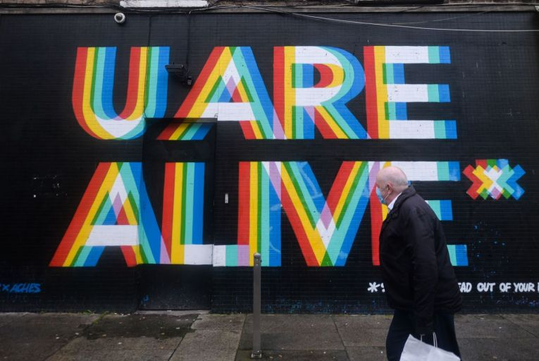 A man wearing a mask walks by a mural \'U ARE Alive, a collaboration between two artists Maser and Aches: Brighter days are ahead in post-Covid-19 times. Picture: Artur Widak/NurPhoto